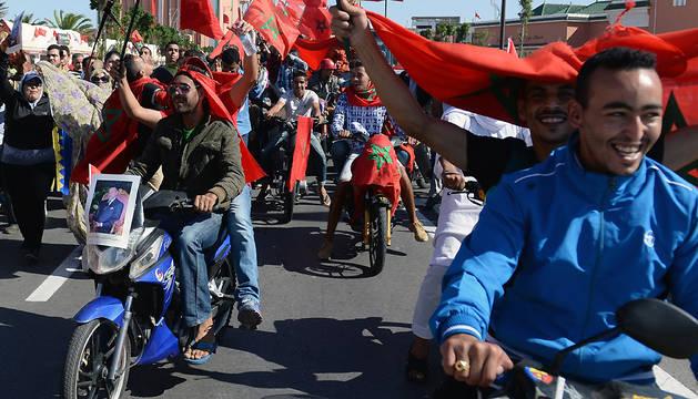 Un grupo de personas celebra con banderas de Marruecos el 40 aniversario de la Marcha Verde.