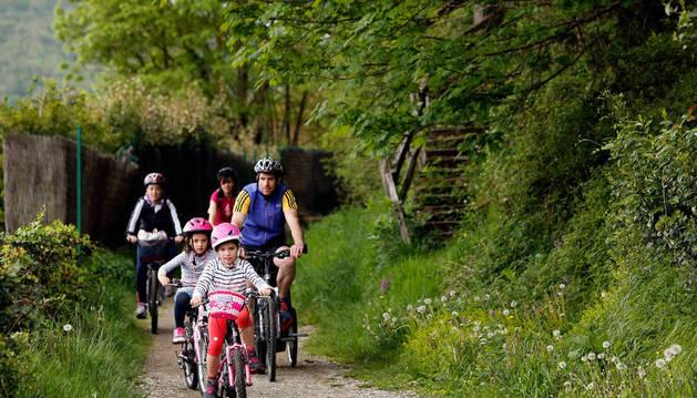 Dos menores acompañados circulan en bicicleta por la vía verde del Bidasoa.