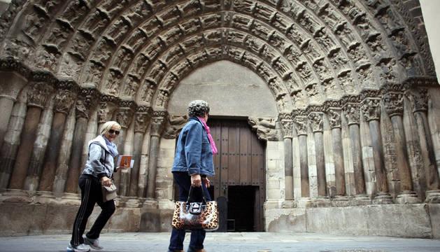 Dos vecinas pasan ante la emblemática Puerta del Juicio de la Catedral de Tudela, construida entre los años 1215 y 1230.