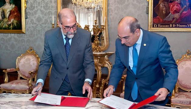 Los consejeros de Salud de Navarra y País Vasco, Fernando Domínguez y Jon Darpón, firman el acuerdo de colaboración.
