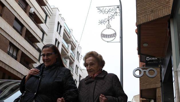 Dos mujeres caminan por la calle Pablo Sarasate con un adorno colocado en la farola a sus espaldas.