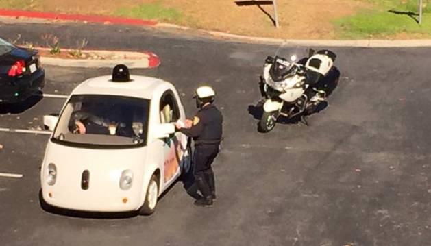 El agente junto al coche autónomo de Google.