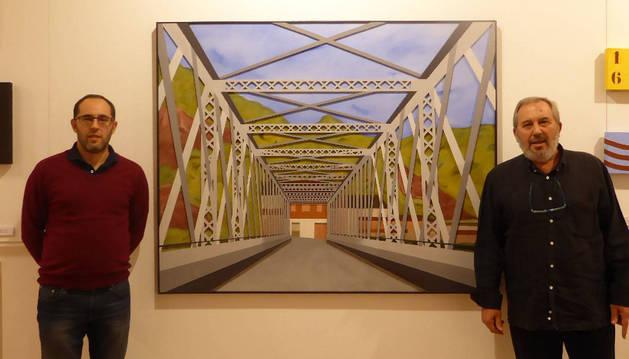 El artista Eduardo Córdoba Oronoz junto a su hijo Fermín y uno de los cuadros de la muestra.