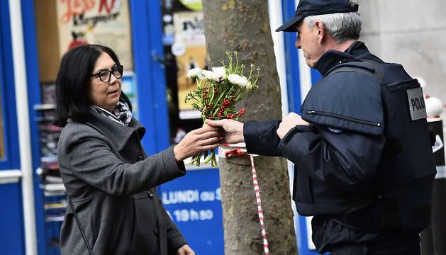 Una parisina entrega flores a un policía cerca del lugar de uno de los atentados, en la Rue de Charonne.