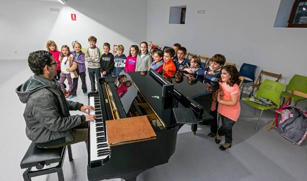 Alumnos de coro de la escuela de música, en el nuevo salón de actos que ya usan pero aún pendiente de equipar.