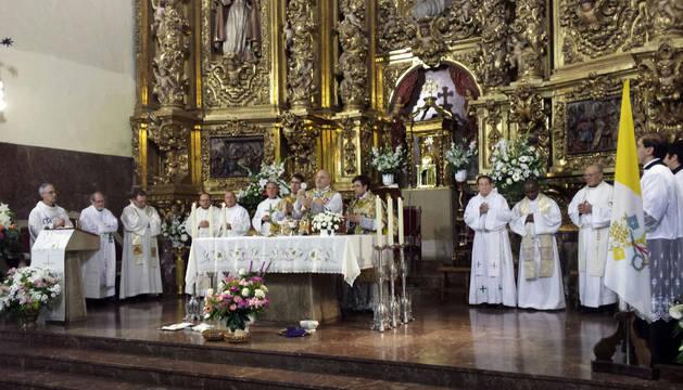 El párroco de Azagra, Pedro José Hernández, en el momento de la consagración, rodeado de los 13 sacerdotes con los que concelebró.