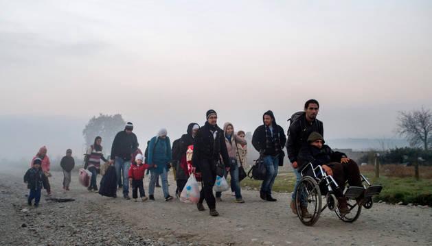 Un grupo de refugiados camina tras cruzar la frontera entre Grecia y Macedonia.