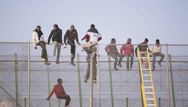 Varios inmigrantes, encaramados a la valla en un intento anterior.