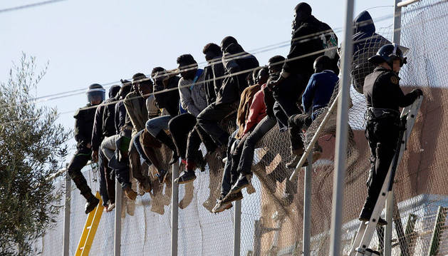 Subsaharianos encaramados a la valla de Melilla.