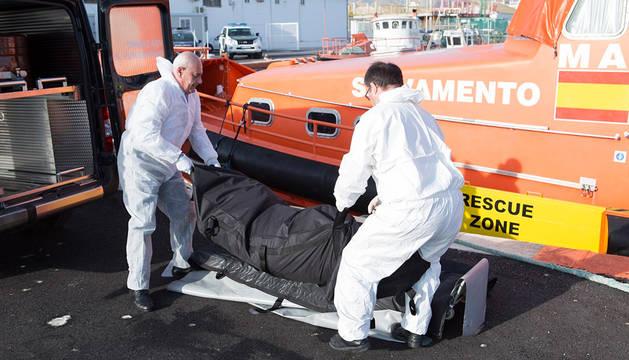 Dos operarios sujetan el cuerpo sin vida de una mujer encontrada en Motril.