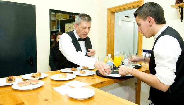 Dos personas, trabajando como camareros en el bar.