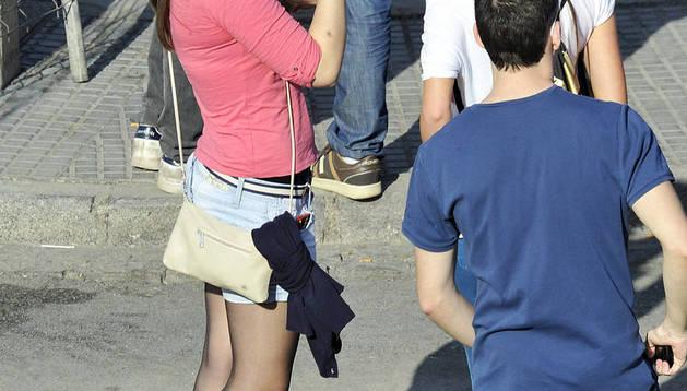 Jóvenes esperan en la calle con varias bebidas alcohólicas y refrescos.