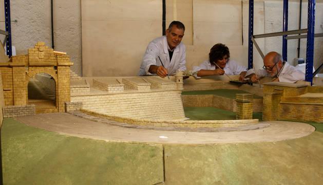 Tres belenistas trabajan en el nacimiento que recrea parte de la muralla de Pamplona.