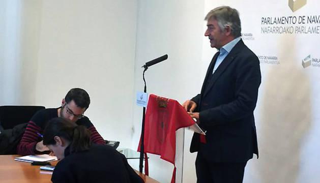 Koldo Martínez realiza declaraciones con la bandera de la Comunidad foral en el atril de la Cámara.