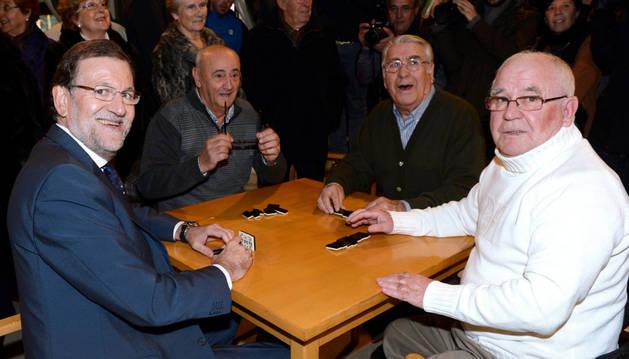 El presidente del Gobierno, Mariano Rajoy, junto a sus compañeros de juego momentos antes de disputar una partida de dominó.