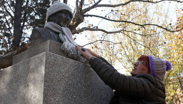 Fefa Blanco coloca a la estatua del Padre Lasa un gorro y una bufanda.