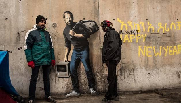Un refugiado observando la última creación de Banksy.