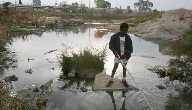 Un niño juega en agua contaminada en el extraradio de Johannesburgo.