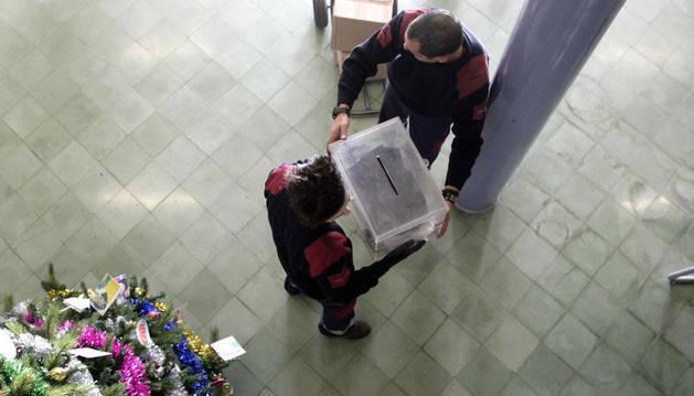 Dos trabajadores de los almacenes municipales de Barcelona colocan una urna en un instituto.