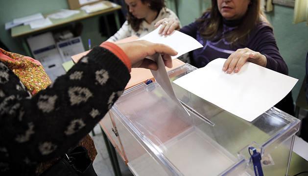 Una mujer deposita su voto en un colegio de Carabanchel (Madrid).