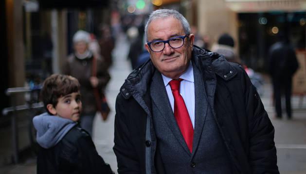 Un niño se vuelve para mirar al presidente de Osasuna, Luis Sabalza, a su paso por la calle San Nicolás de Pamplona.