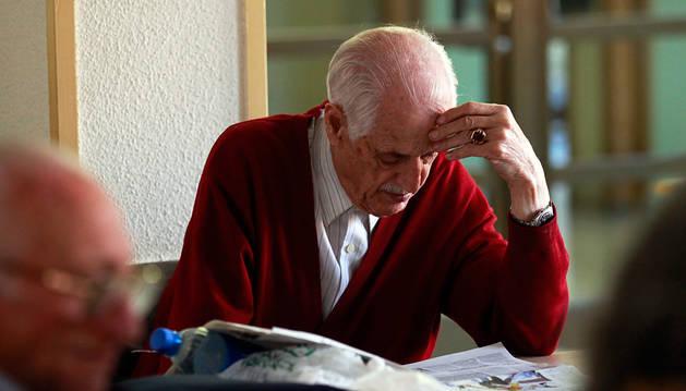 Un jubilado lee un periódico.