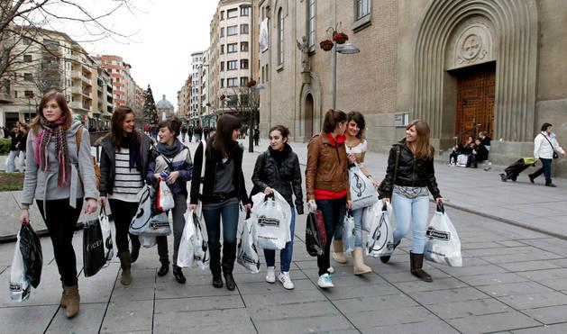 Un grupo de jóvenes camina con sus compras por una de las calles comerciales de Pamplona
