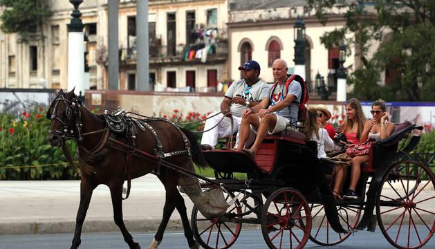 Turistas viajan en un coche de caballos en La Habana (Cuba).