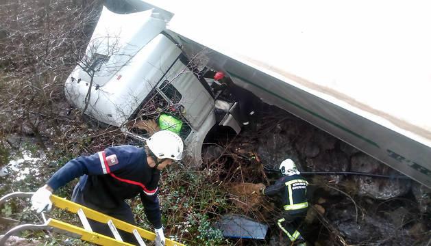 Los bomberos se disponen a rescatar al conductor herido.