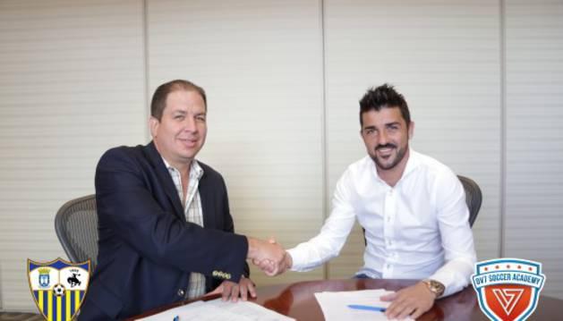 El presidente del Bayamón FC y David Villa firman el acuerdo de colaboración.
