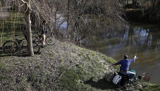 Un pescador intenta capturar algún pez desde la orilla del río Arga en Pamplona.