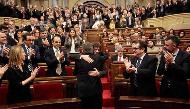 Artur Mas (de espaldas), saluda a Carles Puigdemont al inicio del pleno.