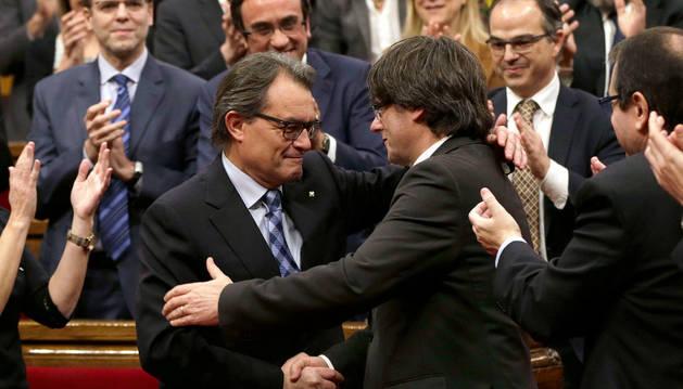 El expresidente de la Generalitat en funciones, Artur Mas (i), felicita a su sucesor, Carles Puigdemont.