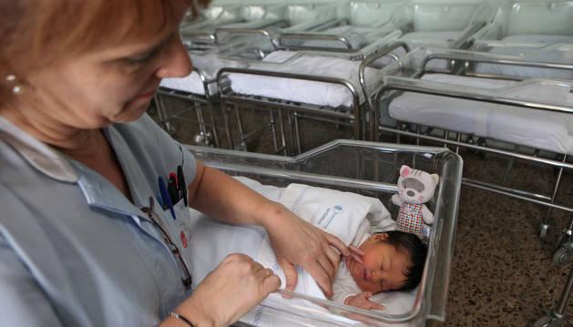 Una trabajadora del hospital atiende a un recién nacido.