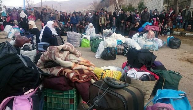 Un grupo de personas espera el transporte para abandonar la ciudad de Madaya.