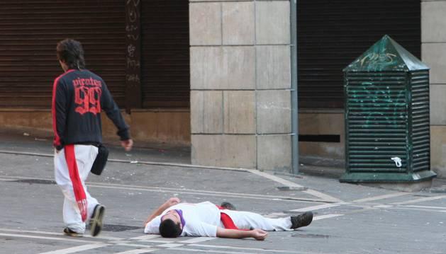 Un joven duerme la resaca en la calle en San Fermín
