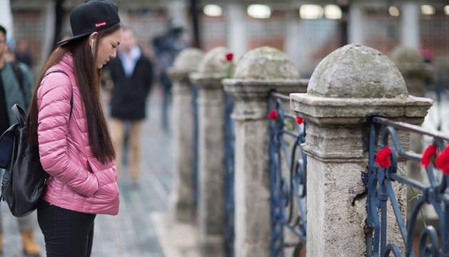 Una turista se detine ante las flores rojas depositadas en homenaje a las víctimas del atentado.