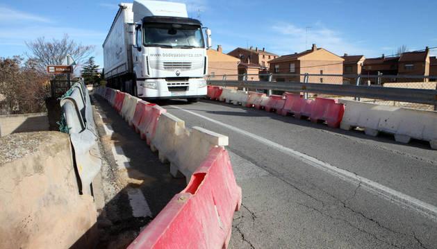 Un camión pasa por el puente de Fitero en el que el Gobierno ha limitado el paso por daños estructurales.
