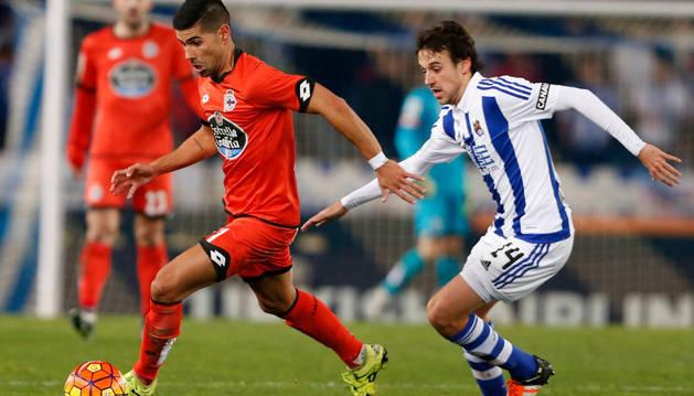 El jugador del Deportivo de La Coruña Juanfran (i) escapa de Rubén Pardo, de la Real Sociedad.