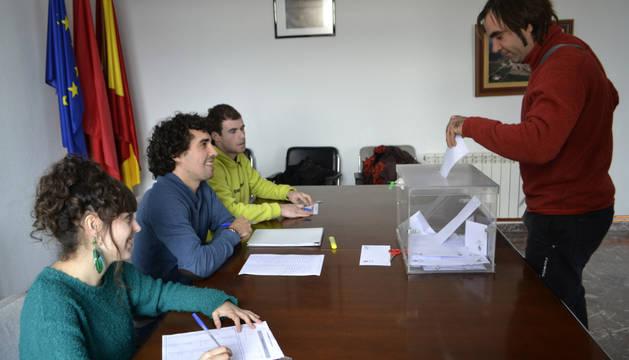 Uno de los 268 votantes introduce su papeleta en la urna ante la mesa electoral formada por Saioa Llorens Barragán, vocal; Álvaro Marquínez Ruiz de Larraga, presidente; y Eder Larrea Sáenz, vocal.