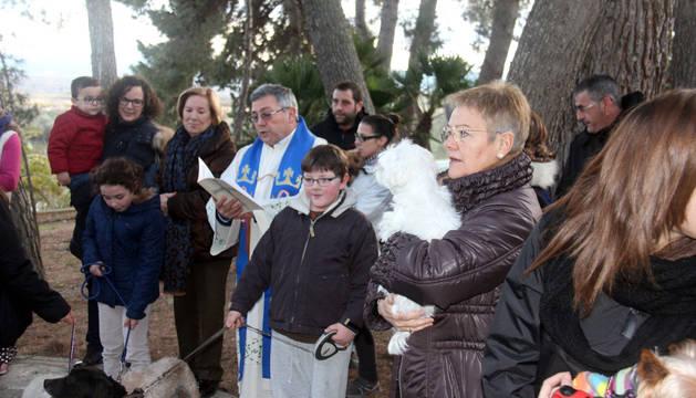 Varias personas con sus mascotas escuchan la bendición del párroco, Santiago Jiménez.