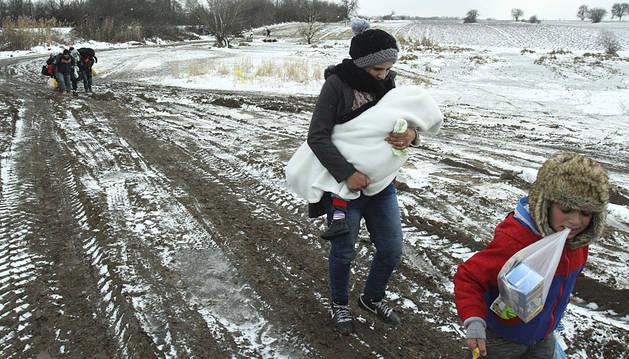 Refugiados de Siria, Irak y Afganistán caminan por un campo helado hacia un campamento en Serbia.