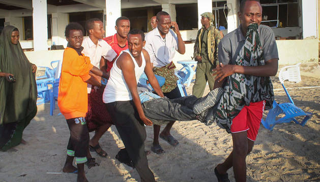 Varias personas trasladan a un herido tras el atentado al hotel somalí.