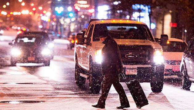 Un hombre cruza una calle nevada en Washington DC, en alerta ante la llegada de la tormenta Jonas.