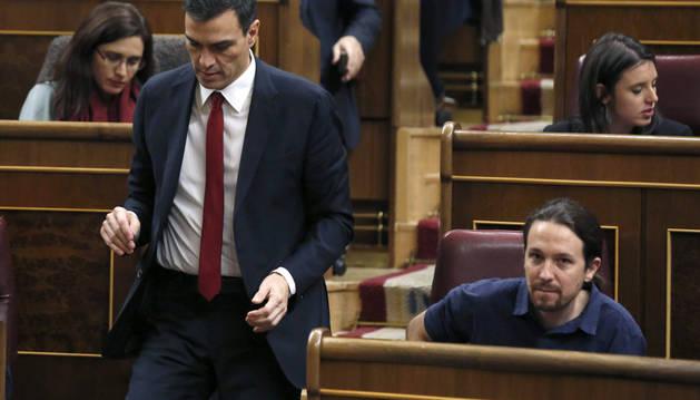 El secretario general del PSOE, Pedro Sánchez pasa junto al líder de Podemos, Pablo Iglesias.