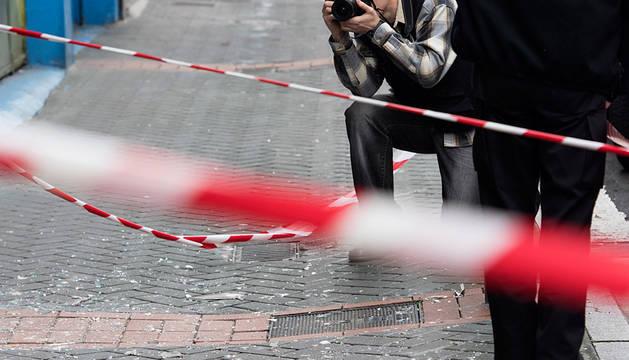 Un ertzaina toma fotografías en la entrada del domicilio.