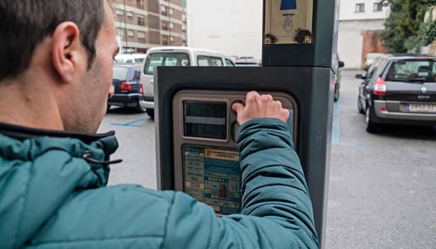 Un usuario introduce monedas en el aparcamiento de zona azul del solar de la Inmaculada.
