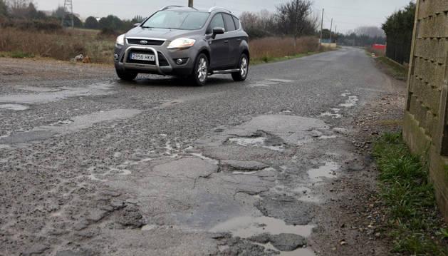 Un vehículo circula por el camino del Instituto por un tramo cuyo firme se encuentra lleno de baches.