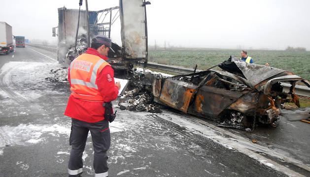 Un policía foral observa los restos de los dos vehículos accidentados.