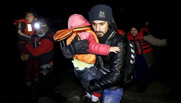 Un hombre afgano llega con un niño a la isla griega de Chios.